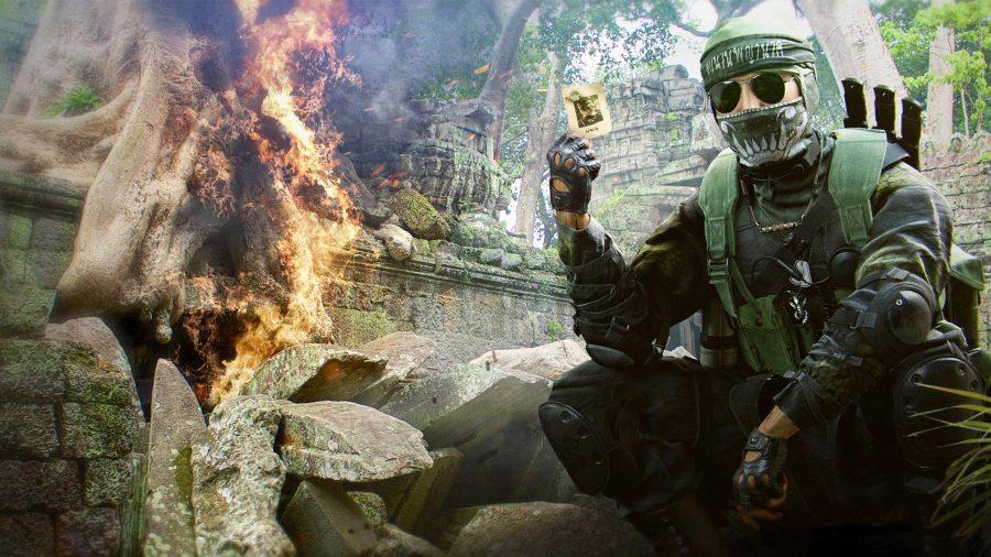 Kapano Naga Vang tenant une carte à jouer pendant qu'un arbre brûle à côté de lui